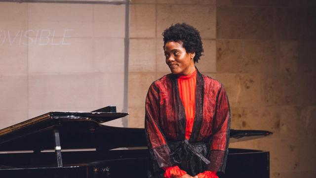 A racially diverse student with a smile in a beautiful red and black dress before a piano